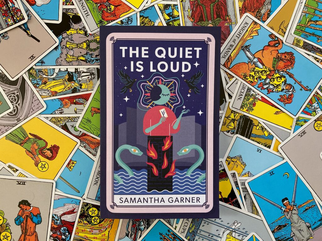 The Quiet is Loud cover on top of an array of cards from the Rider-Waite tarot deck